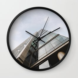 LOW ANGLE PHOTOGRAPHY OF GLASS WALLED BUILDING UNDER WHITE CLOUDS IN THE MORNING Wall Clock