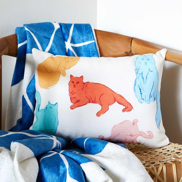 cat throw pillow and blue blanket on a chair