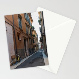 Alley with a colored bicycle parked on one side Stationery Cards