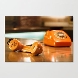 Handset of an orange telephone with dial placed on a wooden table inside a bar. Canvas Print