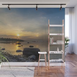 Sun with faint halo over the calm sea and reef rocks Wall Mural