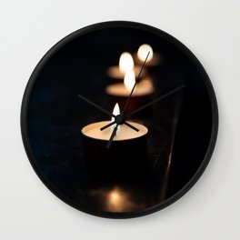Tea candles in a church resting on a dark surface reflect their light Wall Clock