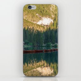 Row of wooden boats in front of a church reflected in the water iPhone Skin