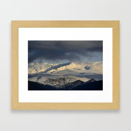 Snowy mountains through the clouds. Framed Art Print