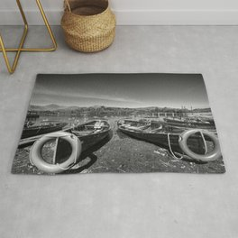Rowing boats on shore of Lake Derewentwater in English Lake District Rug