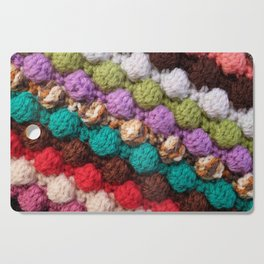 Bobbly colourful knitting craft background Cutting Board