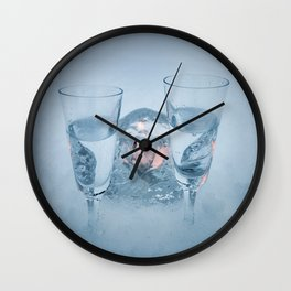 Two vodka shots and cyrstal tealight holder with burning tealight in snow close front view Wall Clock
