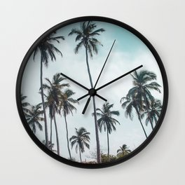 Two towels on the white sand of a beach in Parque Tayrona, Colombia, under tall palm trees Wall Clock