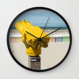 Yellow spotting scope on the beach Wall Clock