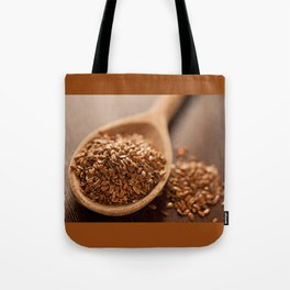 Brown flax seeds heap on wooden spoon Tote Bag