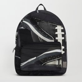 Black gloved hands holding a black American Football Backpack