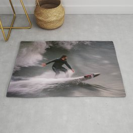 Surfer riding a wave Rug