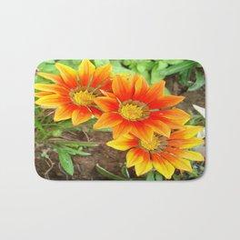 Three Bright Colored Gazania Flowers and Garden Bath Mat