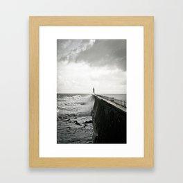 Waves break against an English pier Framed Art Print