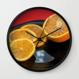 Sliced orange on the black plate and red background Wall Clock