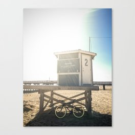 Bike leaning against lifeguard hut on beach Canvas Print