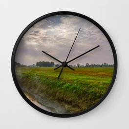 Mist rising from an irrigation ditch in a natural park during autumn Wall Clock