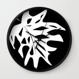 A white sheet of monstera on black background . Wall Clock