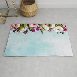 Sweet and colourful doughnuts with sprinkles, purple tulips and berries Rug
