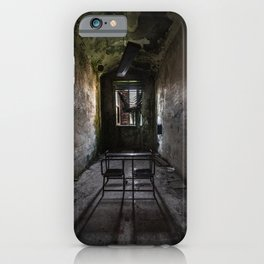 A school desk in a narrow classroom of an abandoned madhouse iPhone Case