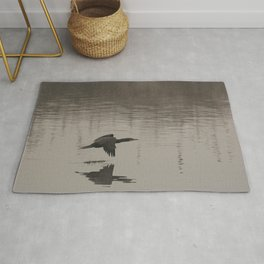 The great cormorant flies at water level over a river Rug