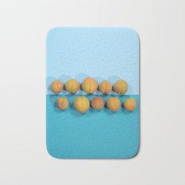 Ripe apricots on a blue background Bath Mat