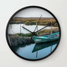 Weathered and abandoned small boat close to shore in peaceful lagoon on bright day. Wall Clock