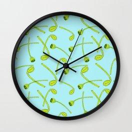 Green poppy flower buds on light blue background Wall Clock