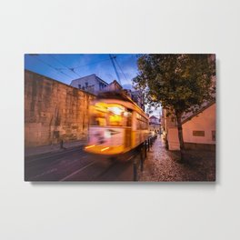 A tram transports tourists through the Alfama District in Lisbon, Portugal at dusk Metal Print