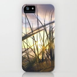 Sun light is coming through green grass in the sun set with sea in the behind and cloudy sky iPhone Case