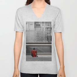 A man in a red shirt sits in front of a fountain Unisex V-Neck