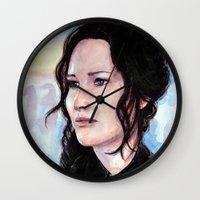 katniss Wall Clocks featuring Katniss Everdeen by Alina Rubanenko