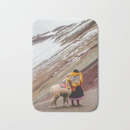 Peruvian girl in Quechua dress with her pet llama in front of a snow-capped Rainbow Mountain Bath Mat