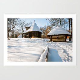 Snow cover in a Romanian Village with an old wooden church Art Print