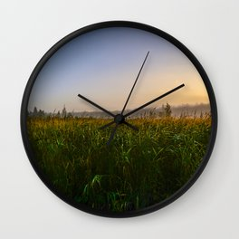 Cloudless sky in the sunlight over a grassy swamp on sunrise Wall Clock
