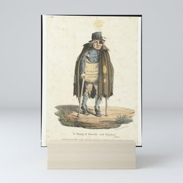 A beggar dressed in ragged clothes walks on crutches begging for scraps. Coloured lithograph by E. H Mini Art Print
