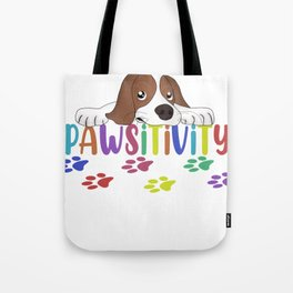 Pawsitivity The cute little puppy is lying on the colorful word Pawsitivity in front of colorful Tote Bag