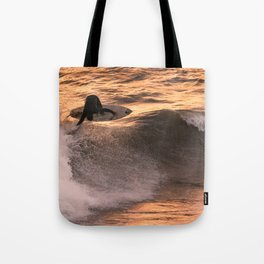 Surfer grabs air on wave at sunset Tote Bag