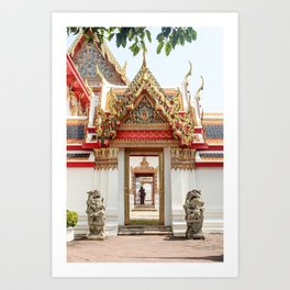 Lion statues guarding doorway to Wat Pho temple. Couple in the distance. Art Print