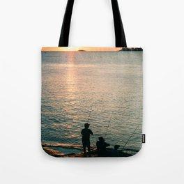 Three fisherman enjoy a beautiful sunset at the shore of 'Colonia del Sacramento, Uruguay'. Tote Bag