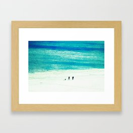 Walking the dog by an aqua-blue ocean Framed Art Print