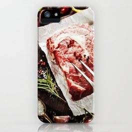 Raw beef steak with meat fork and ingredients on wooden background iPhone Case