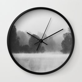 Trees disappearing in morning fog above the lake Wall Clock