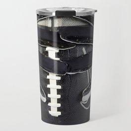 Black gloved hands holding a black American Football Travel Mug