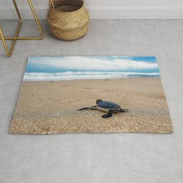 A sea turtle baby aiming at the sea Rug