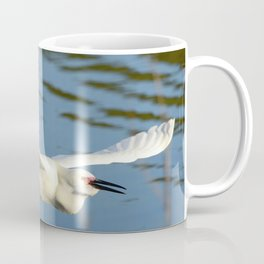 A Snowy Egret wings its way across the lake to a fishing spot Coffee Mug