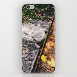 Water flowing through weir covered in autumnal leaves. Norfolk, UK. iPhone Skin