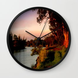 Reflecting sunset on the river Bank Wall Clock