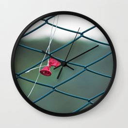 Deflated red balloon on fence net Wall Clock