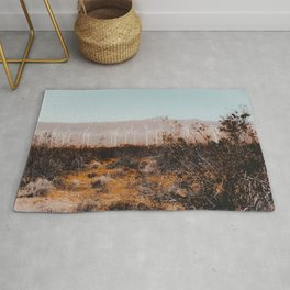 Desert and wind turbine with mountain background at Kern County California USA Rug